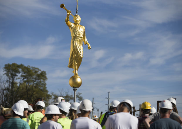 Construction crews prepare to place the Angel Moroni atop the temple
