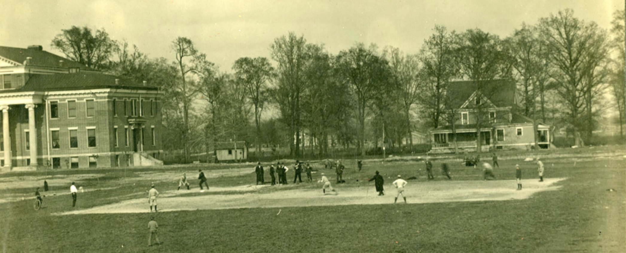 The Greyhounds baseball team practices in a field adjacent to Good Hall (on the left) in this early 20th century photograph.