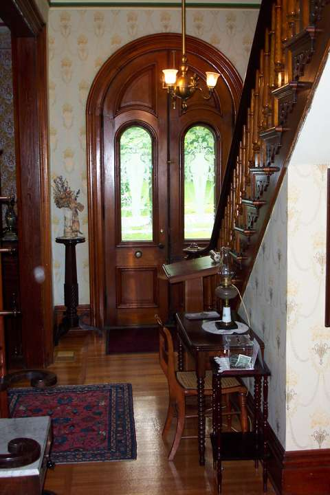 A view of Benton House's foyer, within its tower entrance, to include period furnishings, hardwood floors, and its central staircase.
