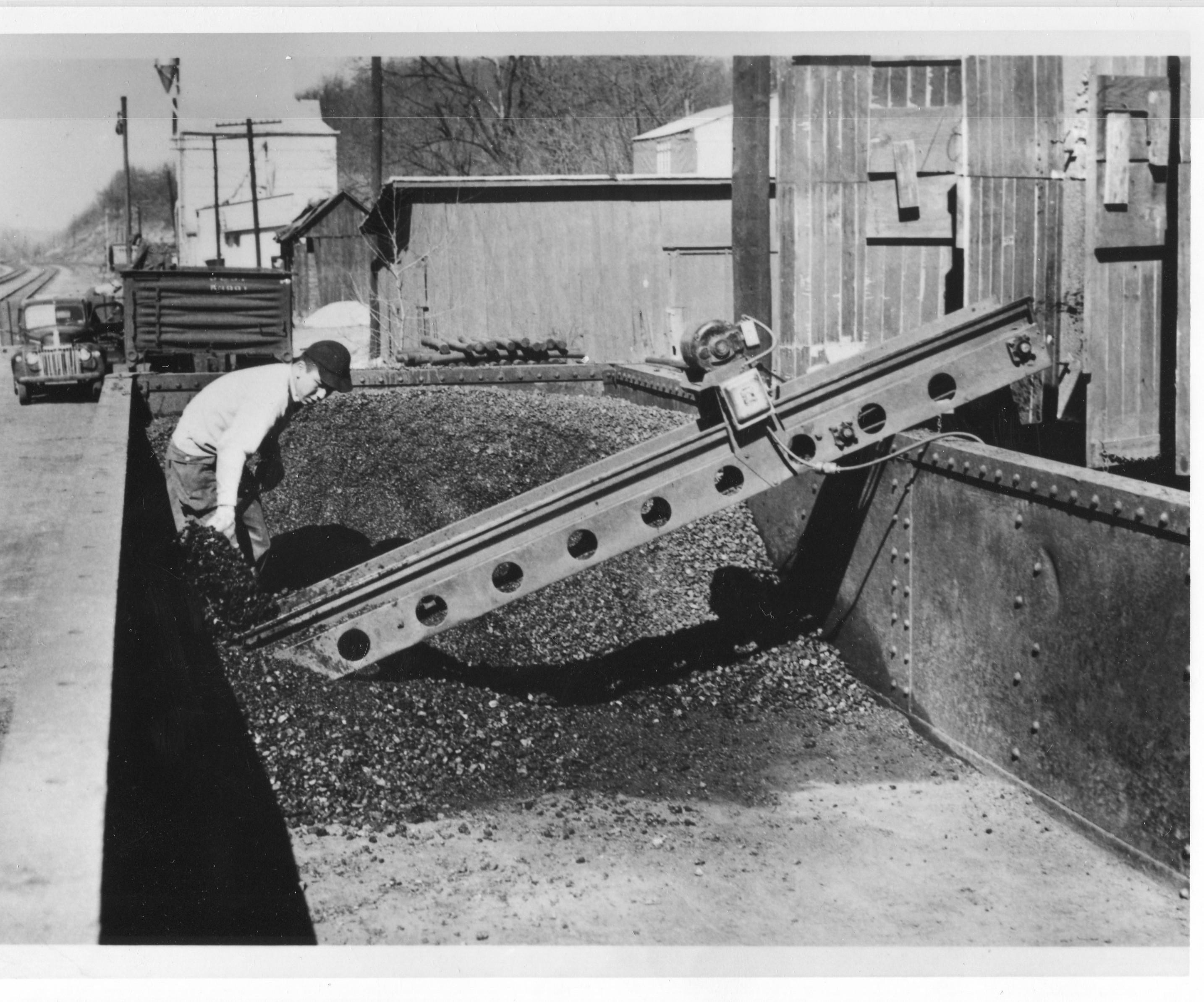 Photo of student shoveling coal into chute.