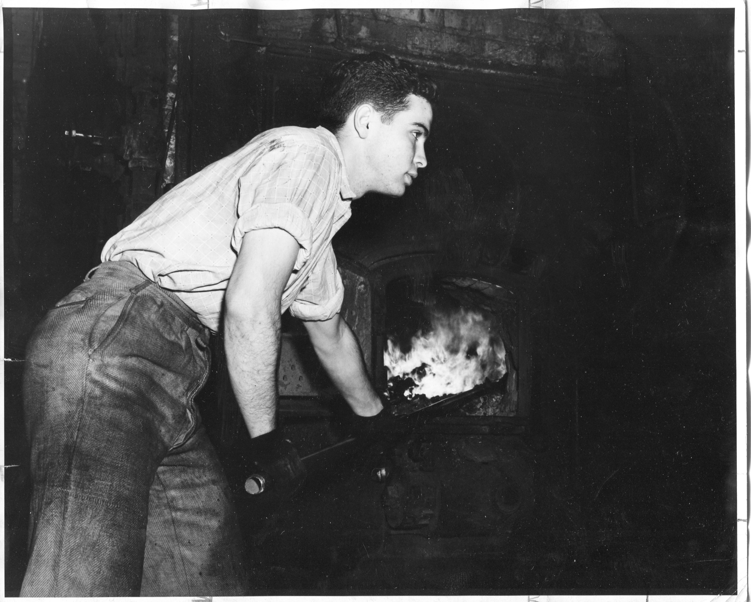 Student loading coal into the furnace.