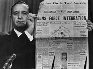 Orval Faubus holds up a local newspaper that interpretted Eisenhower's actions to enforce the decision of the Supreme Court and uphold integration as tyranny