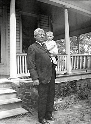 Neal Somers Alexander, pictured with a grandchild, in front of his home's sweeping porch.