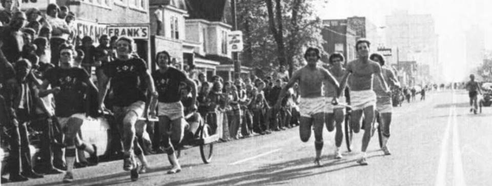 Fraternity members race in chariots past Frank's, 1971