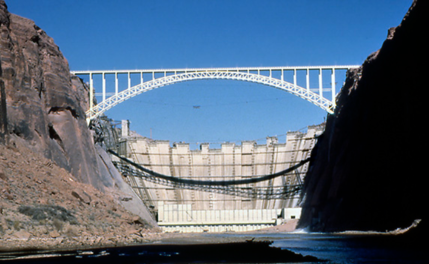 Glen Canyon Dam under construction in 1963. It shows the dividing of the Colorado River. When looking at other pictures, I thought the dam was directly under the bridge, however this picture shows that the bridge is in front of the dam. The bridge was initially for the delivery trucks in order to bring the materials and equipment over the canyon in a short amount of time. An interesting factor of this picture is that it gives you a view at what the dam looked like without the water. Now that it has water, we obviously cannot see what is looks like from that point of view.