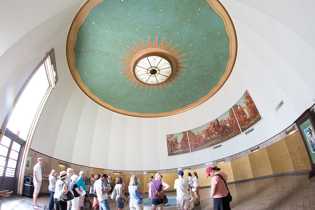 Tourists on a Miami Beach Art Deco tour admire the post office's mural and unique ceiling art.