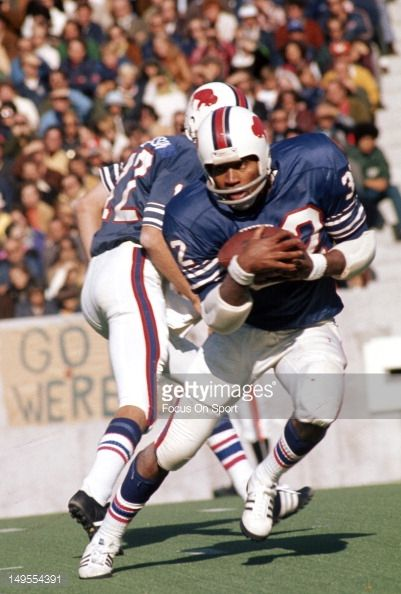 "O.J. Simpson carrying the ball in his home stadium of Rich Stadium. Rich Stadium was overflowing of people wearing Simpson's jerseys and ""Juice"" signs. People across the country came to watch Simpson tear it up on the turf at Rich Stadium."