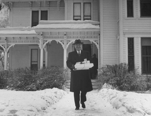 President Truman leaving the house on his way to a family event at Christmas time with presents in tow.