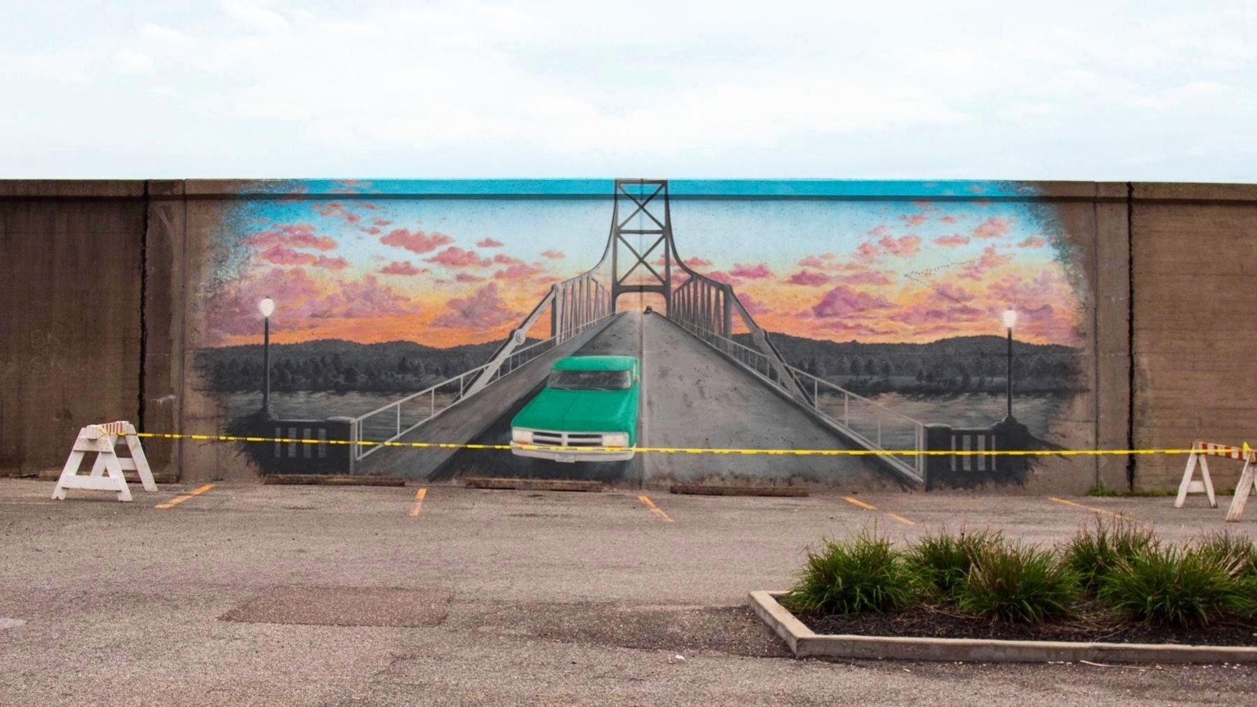 In 2018 a mural depicting the Silver Bridge was painted on the floodwall in front of the memorial. Image obtained from the Historical Marker Database.