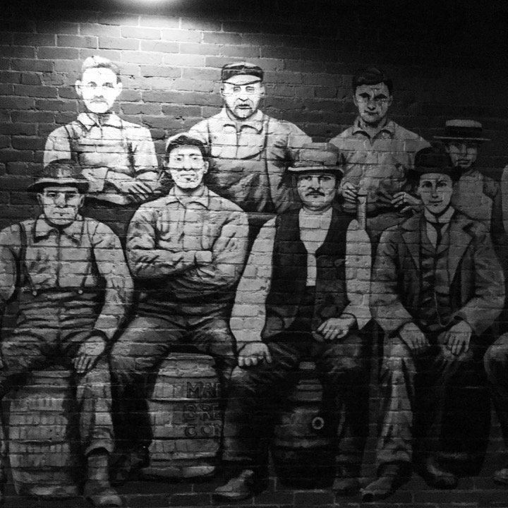 In the mural, Albert Kuehn is on a barrel second from the right in the front row. His sons Albert, George, and John Kuehn are also pictured. They worked at the brewery for a few years and later started the Kuehn Brothers tire and auto parts store.