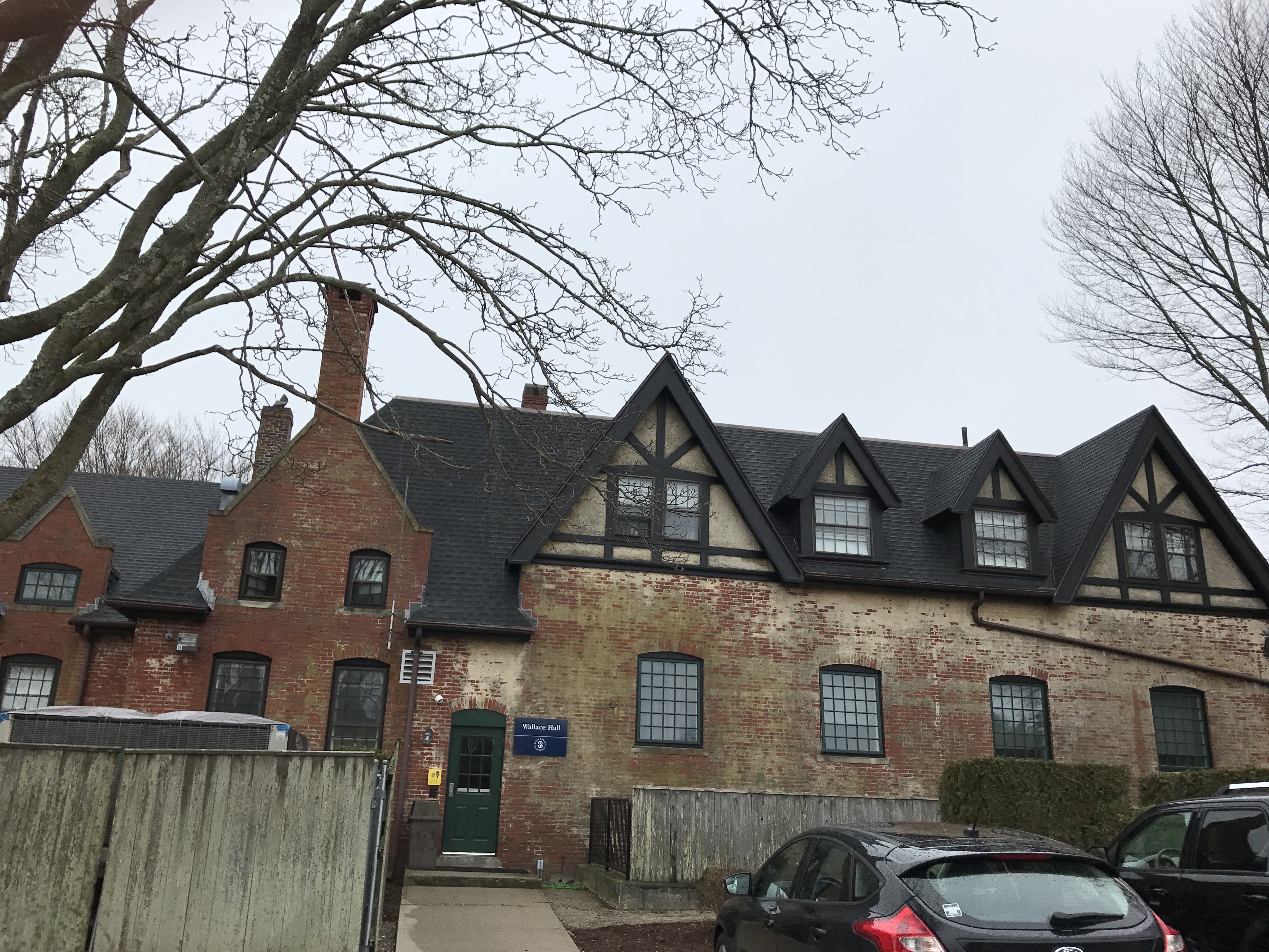 Wallace Hall rear view. Many chimneys, brick and stucco surfaces, steeply pitched roof, and beams shown. All of these are common features of Tudor Revival Style Homes.