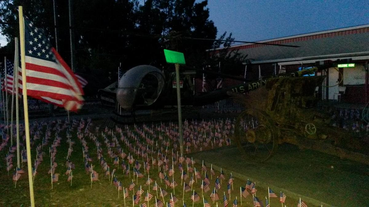 The front entrance to the museum is marked with an old helicopter and American flags adorning the grass, each flag representing one of the fallen soldiers being commemorated.