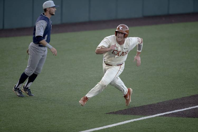 Texas Longhorn player rounds third base as he score the game winning run to win the series in 2019.