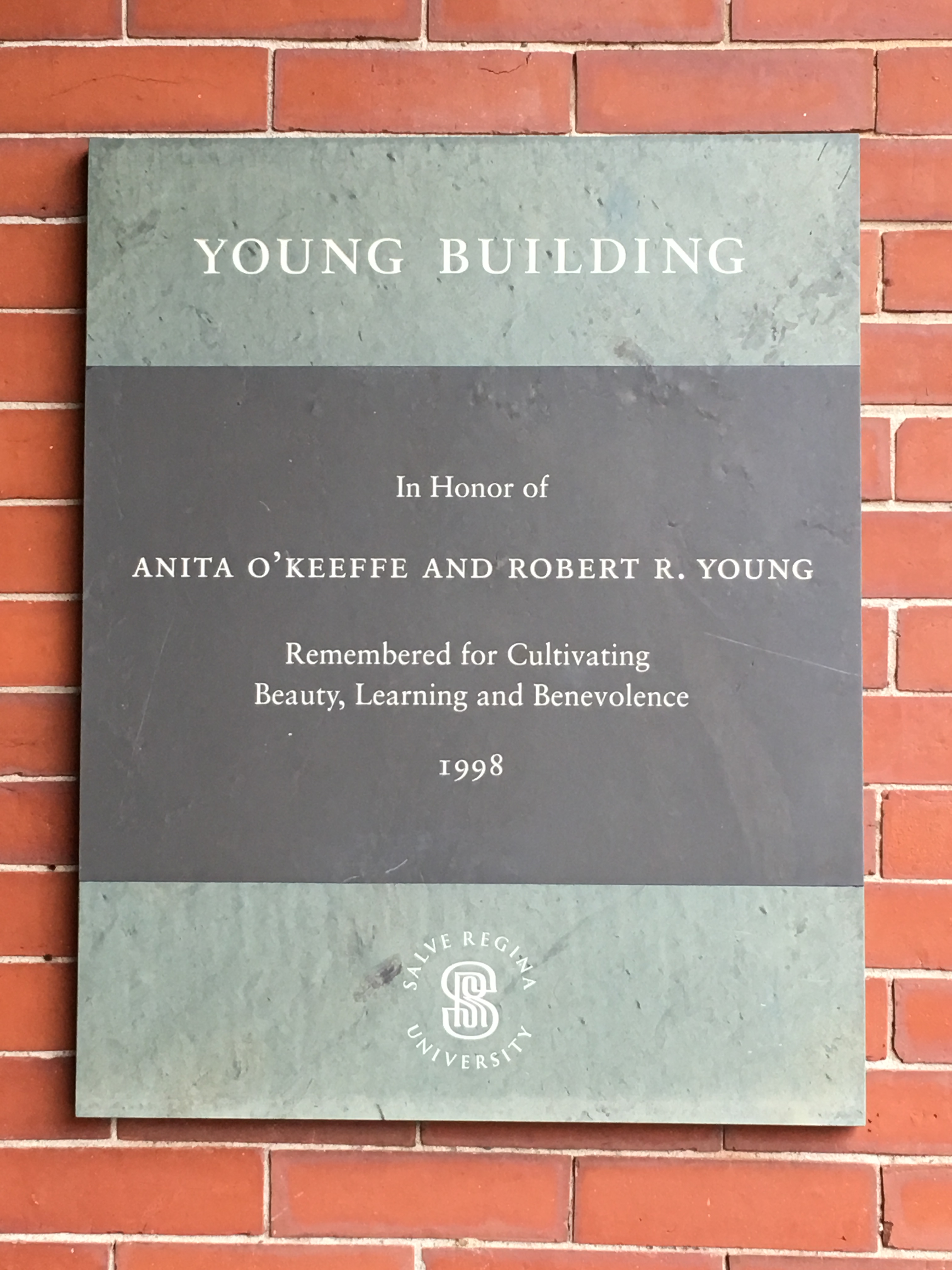 The dedication plaque from Salve Regina University to benefactors Anita O'Keefe and Robert R. Young. This plague faces Bellevue Avenue and hangs to the right of the front door of what is now referred to as the Young Building/ Pell Center.