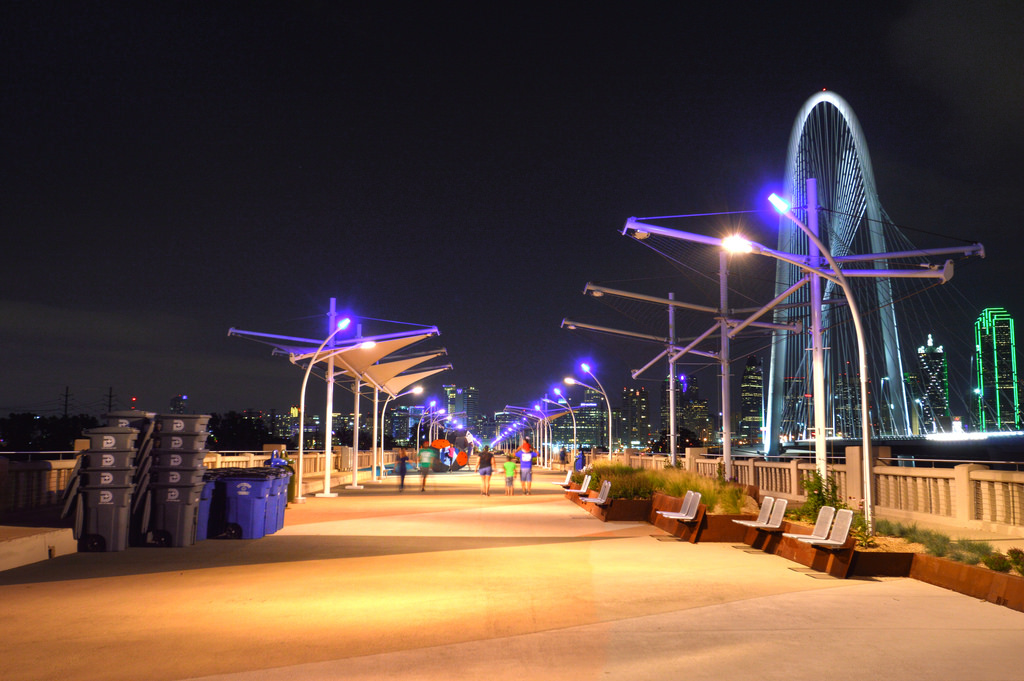 The Kirk and Hill Bridges glow during the evening hours with the Dallas skyline in the background.