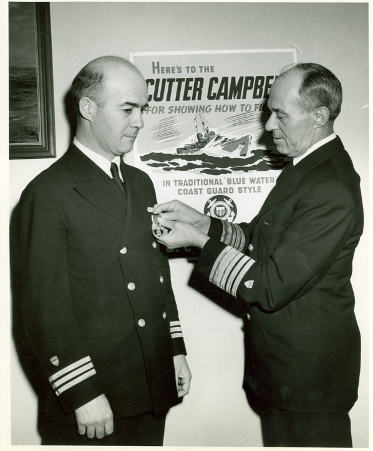 "James A. Hirshfield being awarded the Purple Heart. Hirschfield was Commander of the ""cutter"" ship, Campbell, which is featured in the poster in the background."