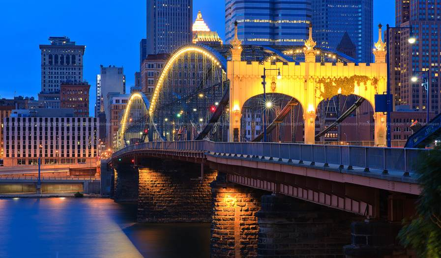 The bridge sporting its original color pattern and updated lighting with the Pittsburgh skyline in the background.