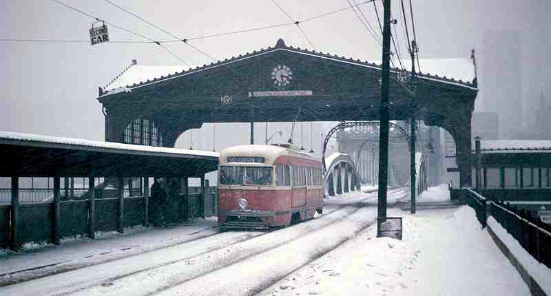 A trolley crosses under the trolley shelter which was removed in 1967.