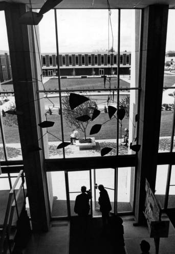 A view from the second floor of the library entry lobby, ca. 1969. In the foreground is a piece of art hanging from the ceiling, and in the background is the Liberal Arts building. The fountain pool is visible between the buildings.