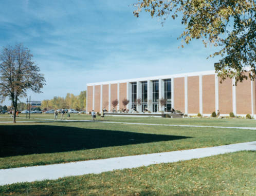 """Color photograph of the front of the library as seen from near the Student Union, ca. 1966. Below the tree on the left is a sign the reads """"Hello Walk."""""""
