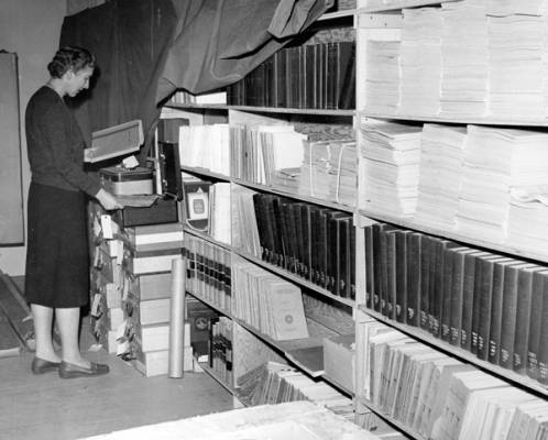 Head Librarian Ruth McBirney with a collection of periodicals in library storage at Boise Junior College, ca. 1961, before the Library Building was built.
