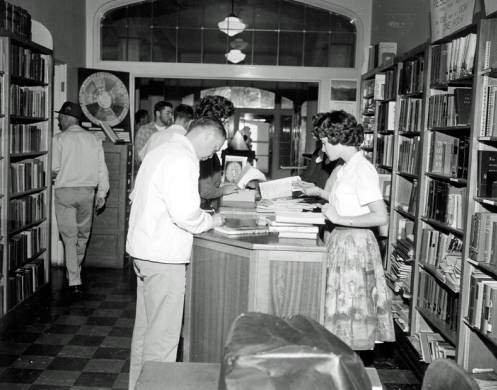 Students checking out books at the circulation desk in the library, when it was still located in the Administration building. The doors in the background are the first floor doors on the east end of the building, ca. 1960.