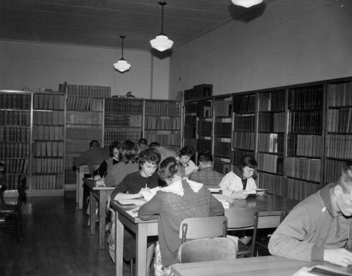 Students using the library to study. Notice the number of chairs per desk. By the early 1960s, the number of students was outgrowing the capacity of many of the buildings on campus. The Library was still located in the Administration building then.