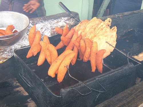 National fried foods being cooked outside and displayed for sale. In the picture, long 'alcapurrias' and rounded 'bacalaitos', two of the most famous fried foods of Puerto Rico, are on display.