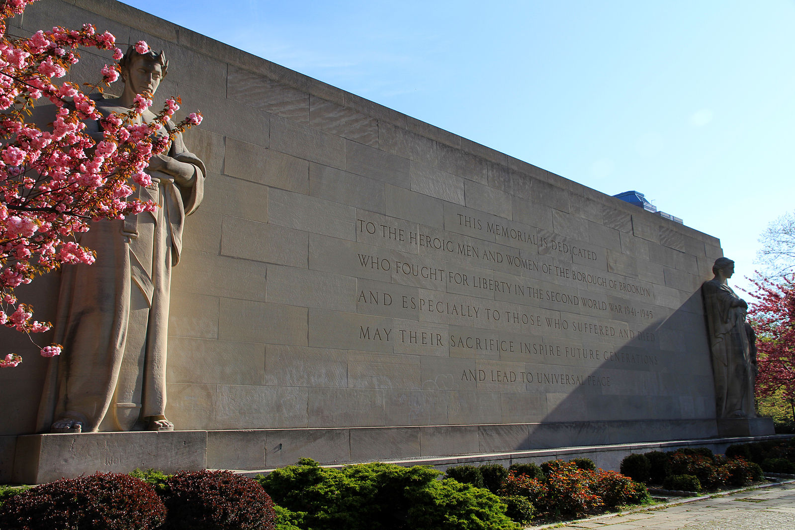 The writing seen in this picture dedicates the monument to the Brooklyn service men and women of World War II.