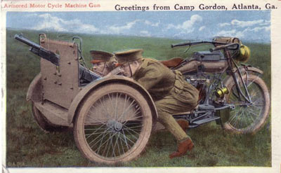 An antique Fort Gordon greeting card of two soldiers standing behind an armored motorcycle machine gun during military training for WWI.