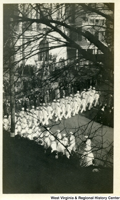 An Armistice Day parade in 1919 marching through downtown. US Navy soldiers pass 211 Willey; the white building in the far background.