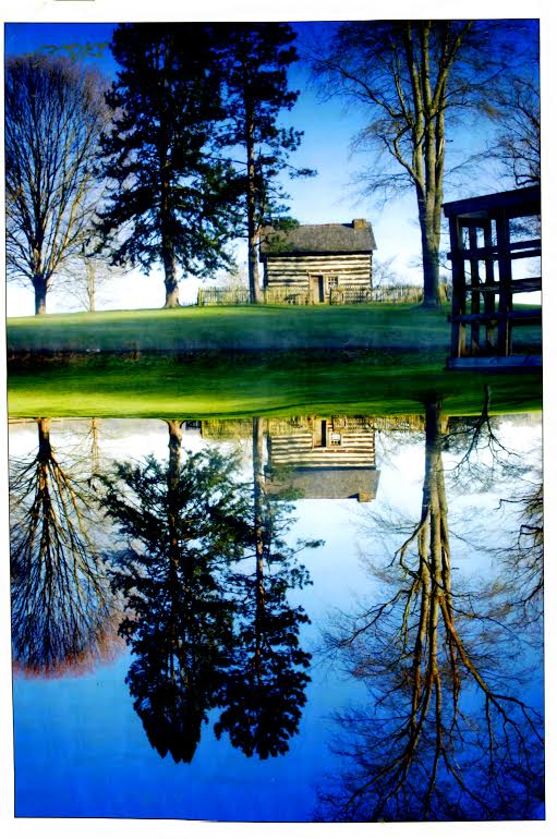 by Robert McWhorter The cabin's image is reflected in the Jackson's Mill Pond, which is used to power Blaker's Mill.