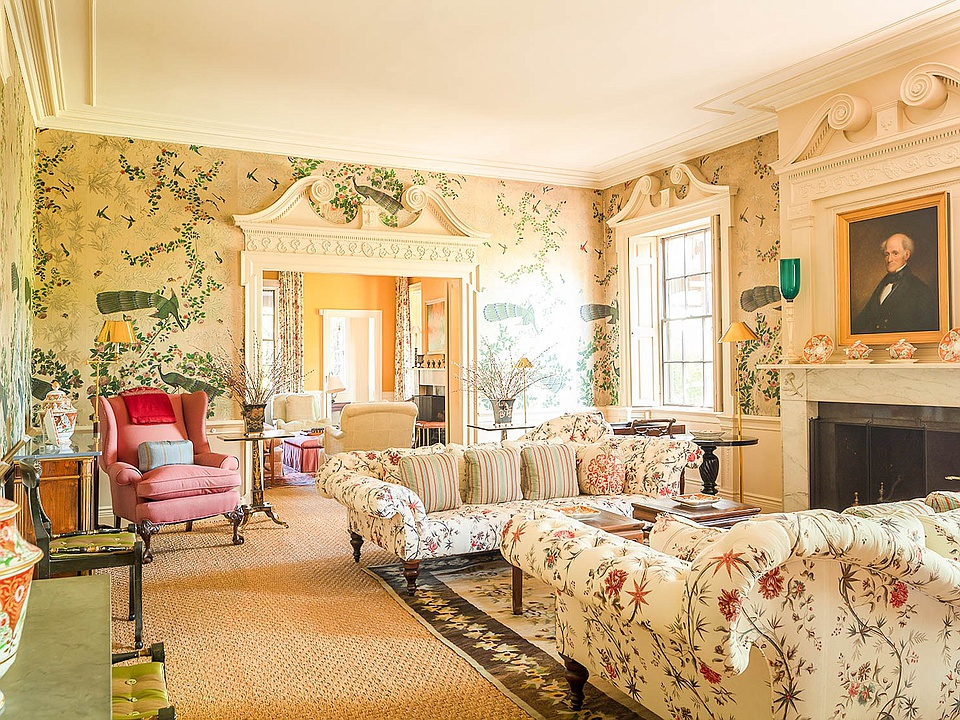 "The first floor parlor that features Chinese ""peacock"" wallpaper installed by Edward Carrington, whose portrait hangs over the mantel to the right."