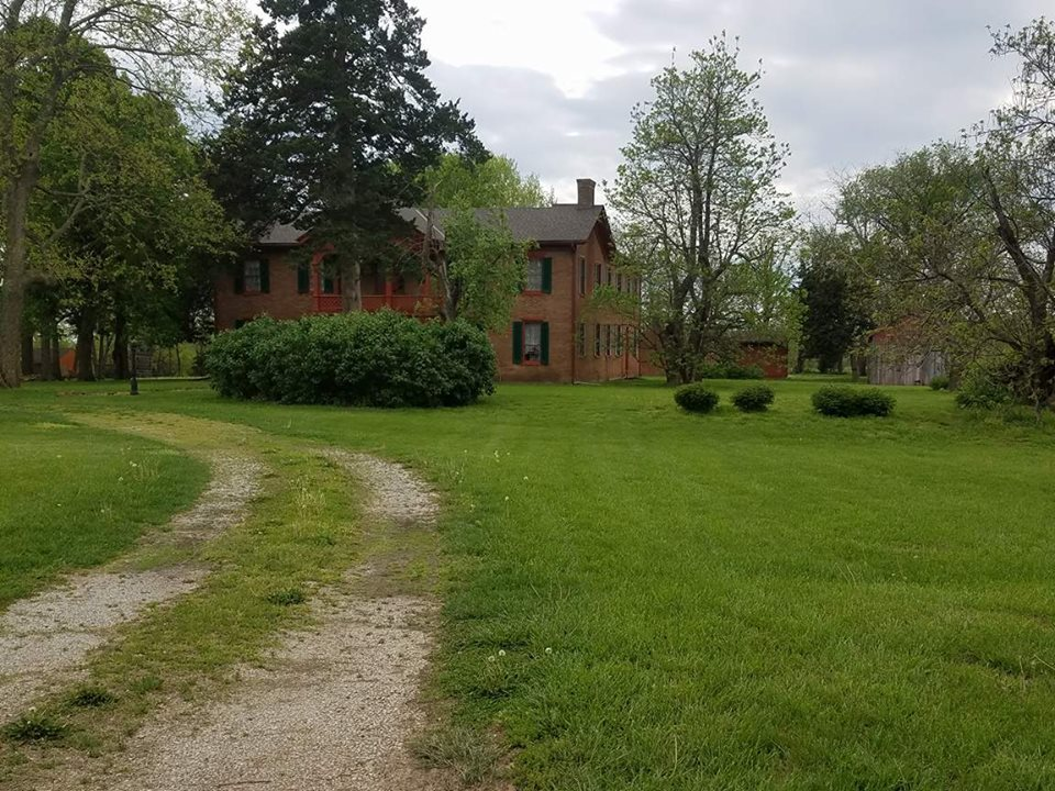 Brown house, yard and out buildings.