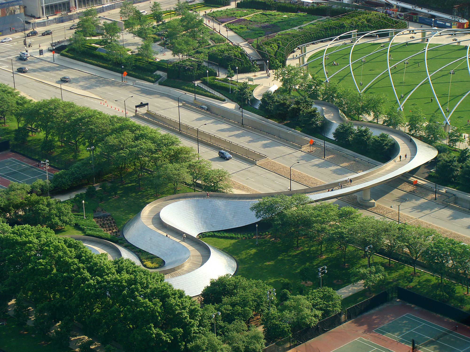 The serpentine form of the BG bridge echoes the smooth curves of nearby Pritzker Pavillion (seen upper right).