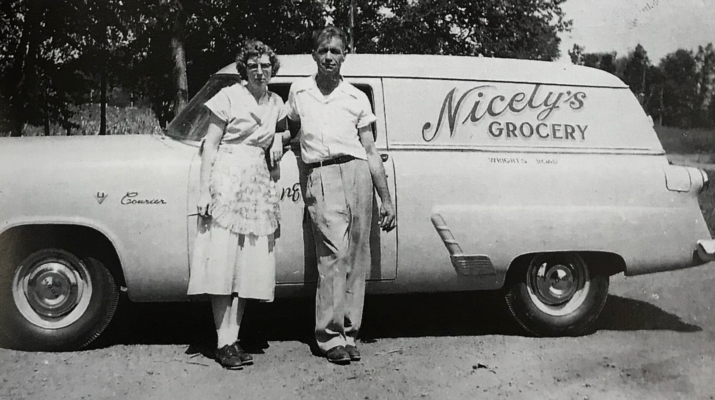 Imelda and Helmer stand next to Nicely Grocery Store Delivery Truck in the 1950s