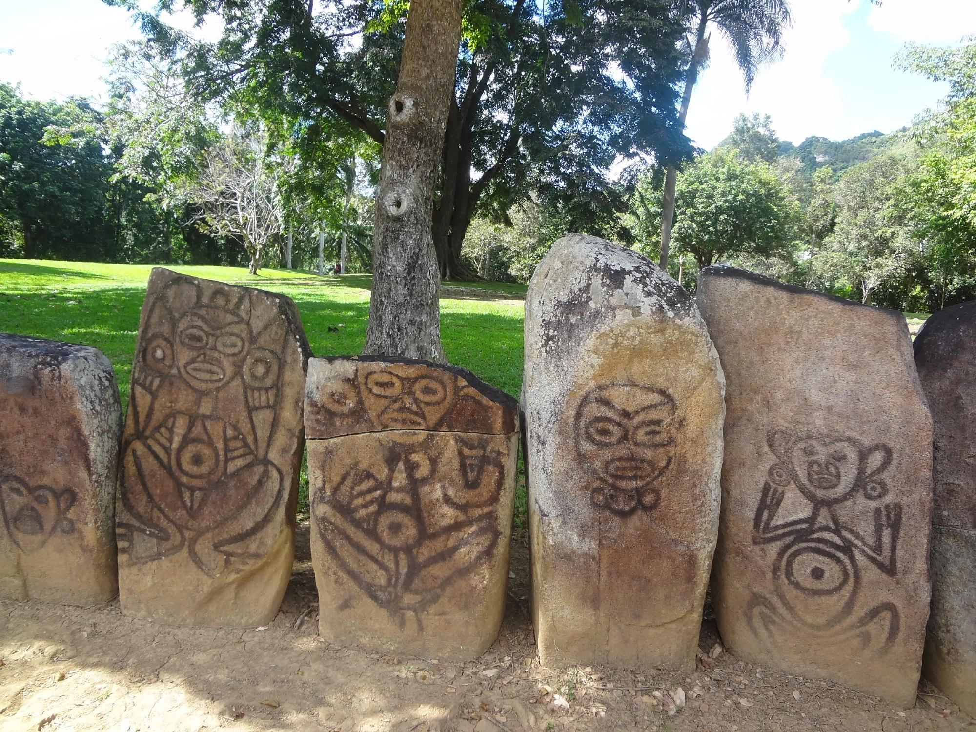 Monoliths painted with petroglyphs of animal figures, human faces without a body, and complete human figures with zoomorphic features.