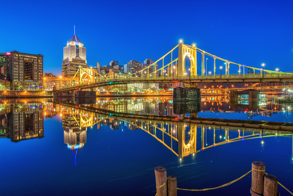 The Clemente Bridge is reflected in the waters of the Allegheny River.  Architectural lighting was added to the bridge in 2002.