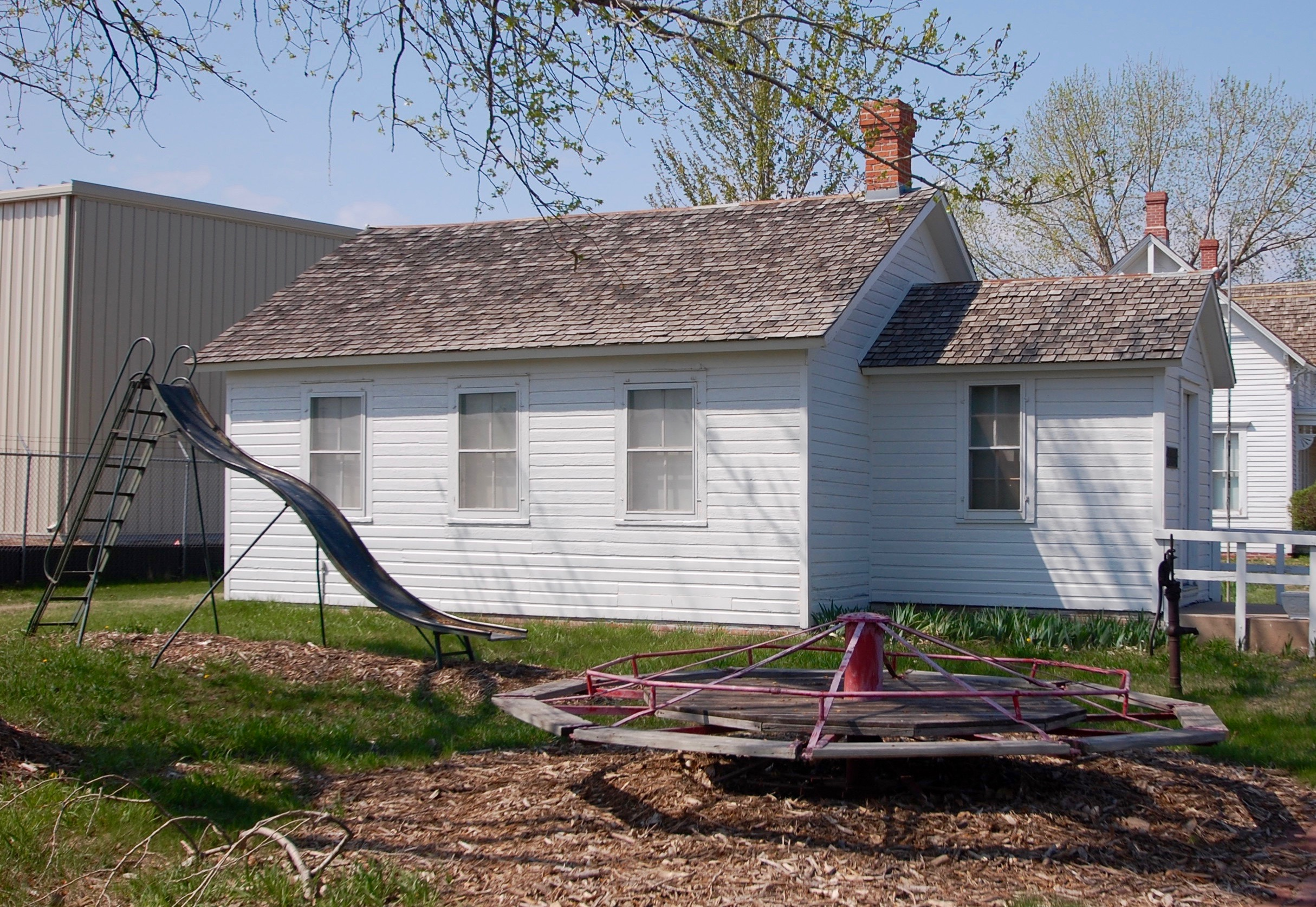Side view of the schoolhouse and playground equipment.