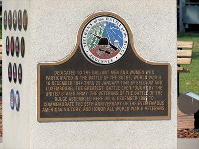 One side of the monument pedestal features a commemorative plaque, while the other sides have the insignias of participating divisions from the Battle of the Bulge. Image obtained from Waymarking.