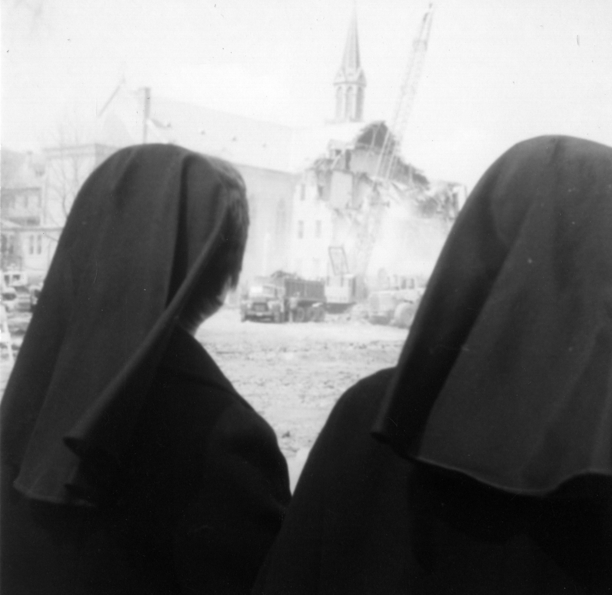 Two sisters watch the demolition of the motherhouse in 1975.