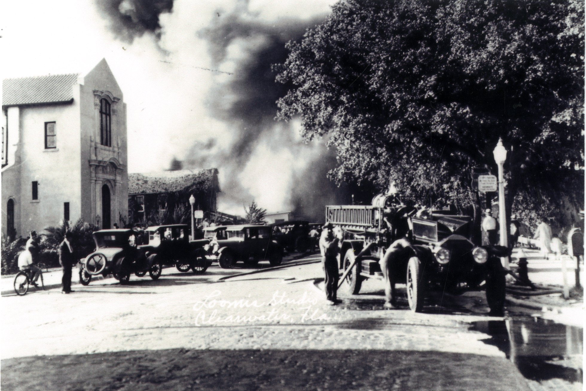 Firefighters and fire engine fighting a fire at the Hart Rug Co. on S. Ft. Harrison St. in Clearwater, Florida, April 28, 1926.