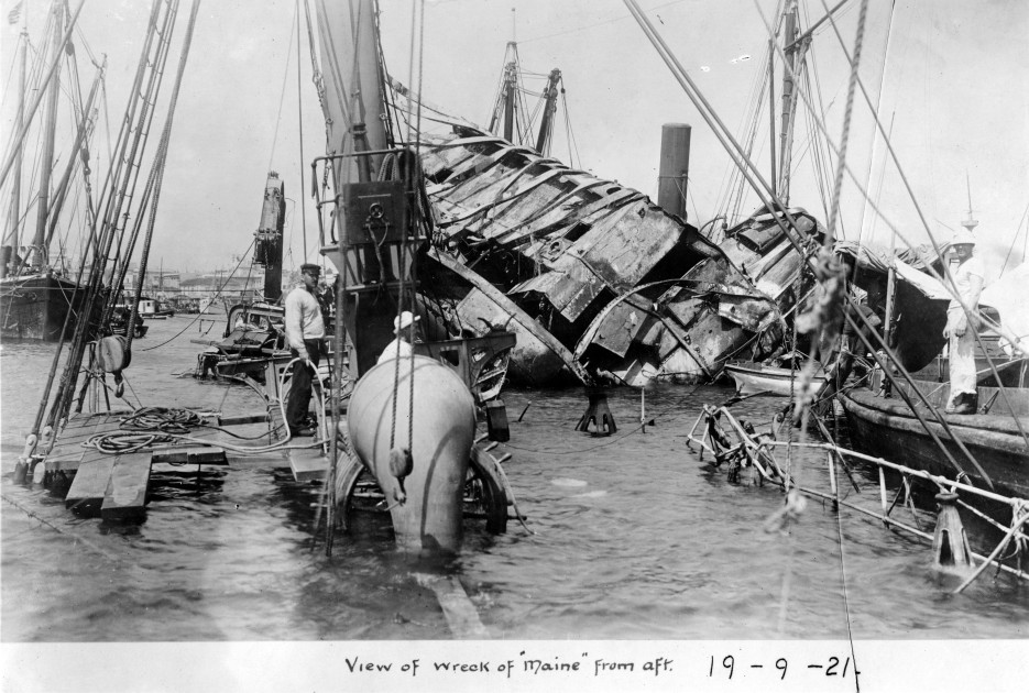 U.S. Navy diving crew at work on the ship's wreck, in 1898, seen from aft looking forward. U.S. Naval Historical Center Photograph.