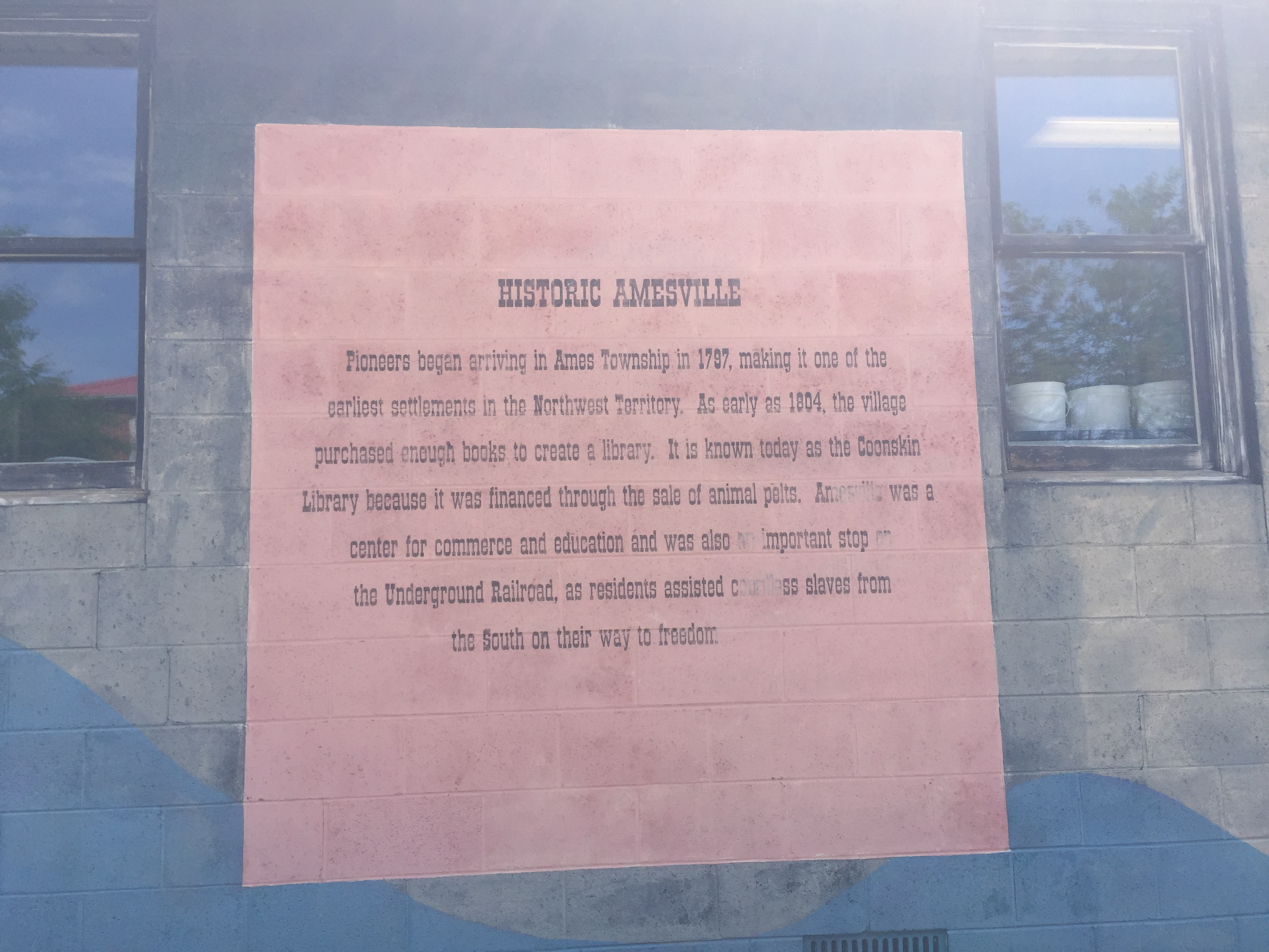 The side of the post office in Amesville hosts this short synopsis of the town's history, including the Coonskin Library and notable tidbit that the town was also a stop along the Underground Railroad. Photo by J Hazen on June 12, 2017.