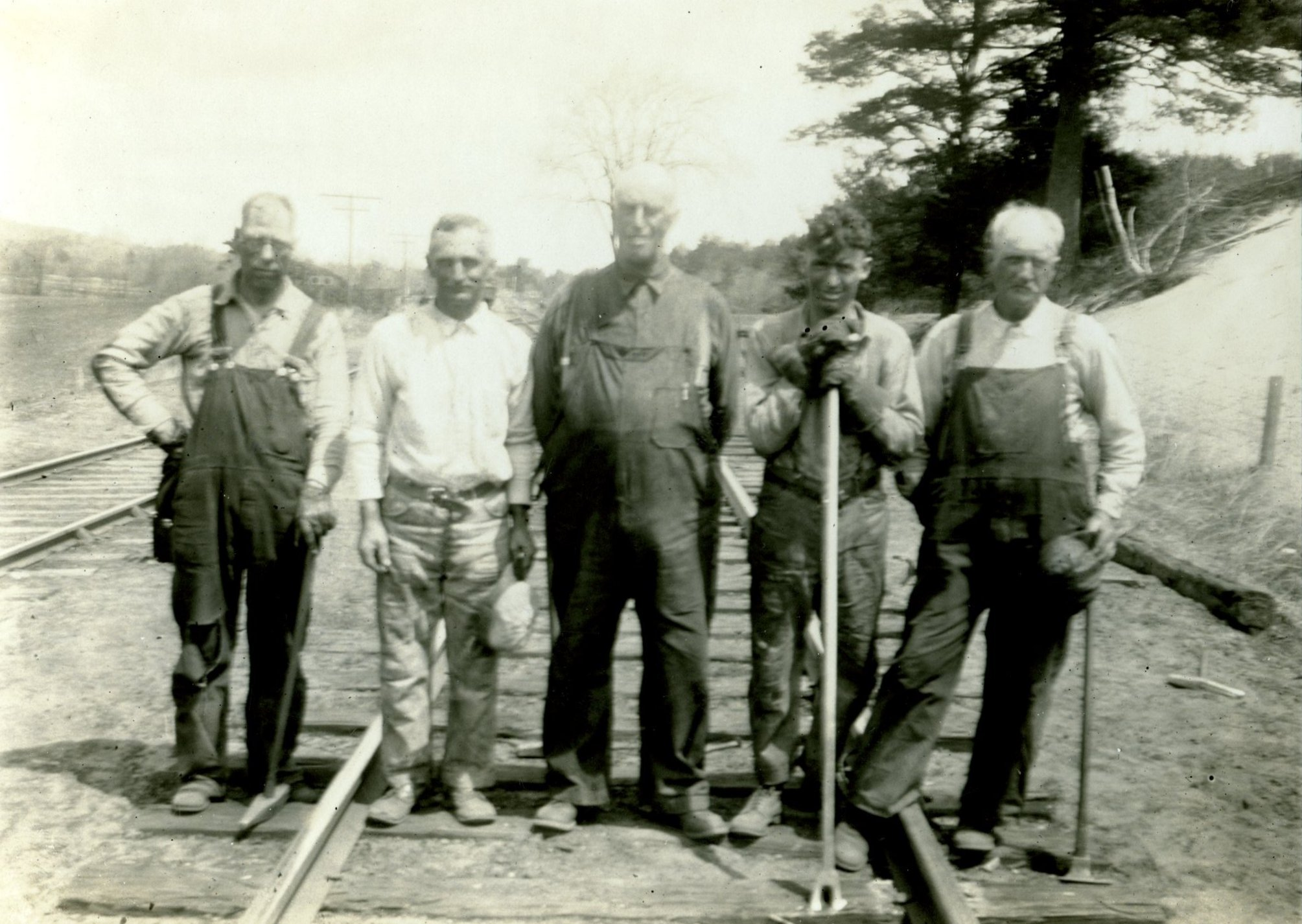 Section gang photo.  One of the two men in the center not holding any tools is likely the foreman.  The man on the left is holding a spike maul that is used to hammer spikes into the ties.  The man second from the right (Theodore Mack of Webster) is holding a spike puller,  a long tool with a forked end used for removing spikes.