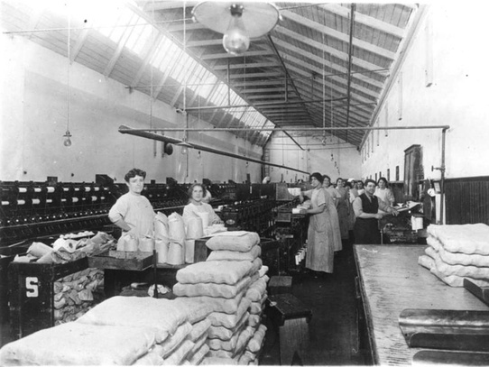 A shot of the Mills' workers spinning and packaging cotton.