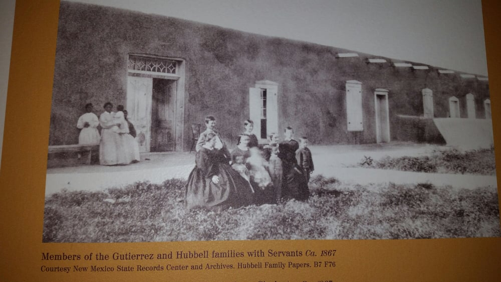 Circa 1867 photo of members of Hubbell family in front of home with servants in back
