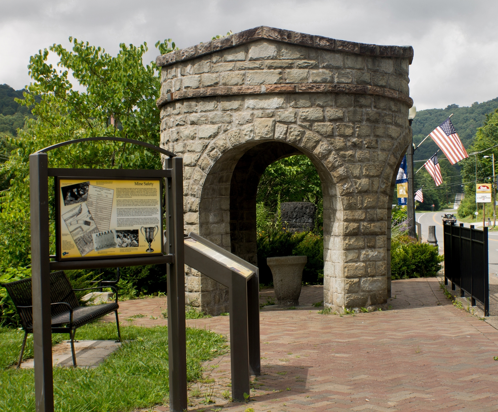 Stone fountain with interpretive signage visible