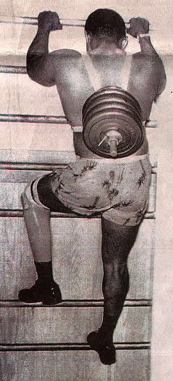 Carl Brashear climbing a ladder with weights attached to his back, part of the training he went through in preparation to be reinstated to diver.