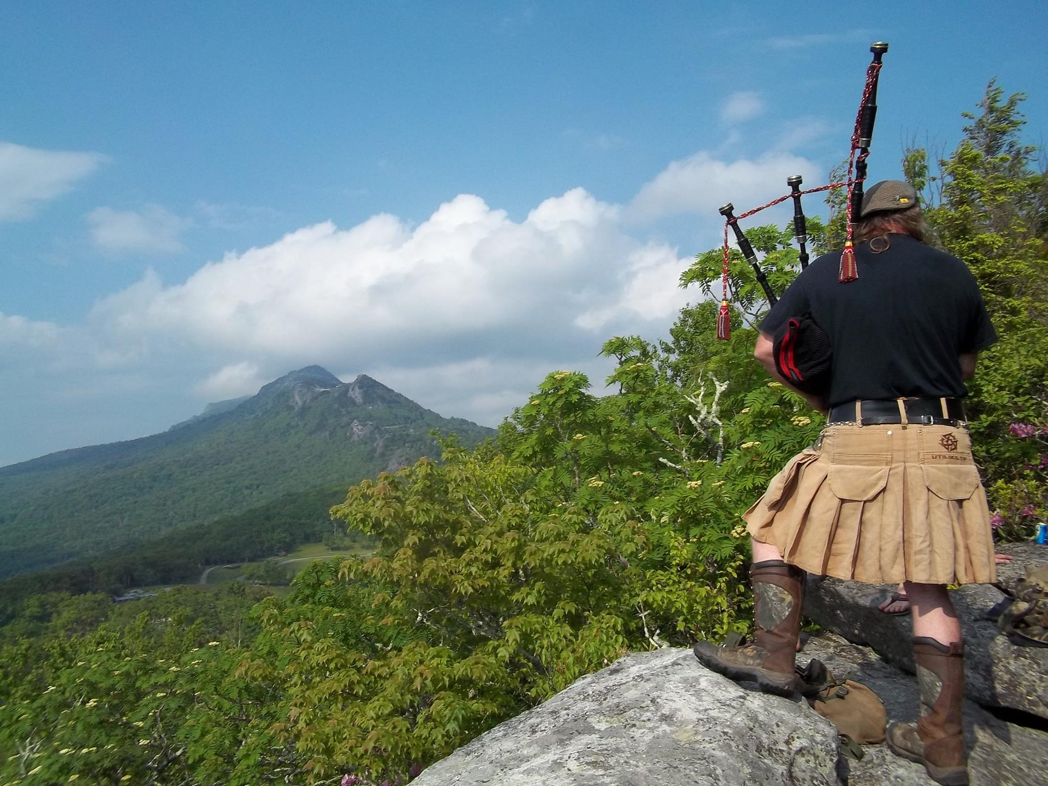 A piper plays from nearby Biscuit Rock above the MacRae Meadow campground.